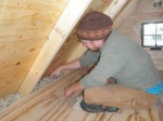 Stuffing the wool insulation in by hand as the walls go up.