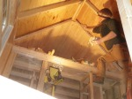 Stuffing wool between rafters in the ceiling.