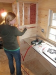 Putting the knotty pine up on a kitchen side wall.