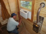 Placing insulation strips under the AC unit.