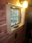 Installing 1X3 cedar trim on bathroom window.